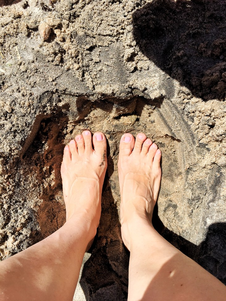 women's feet in a hole in the sand