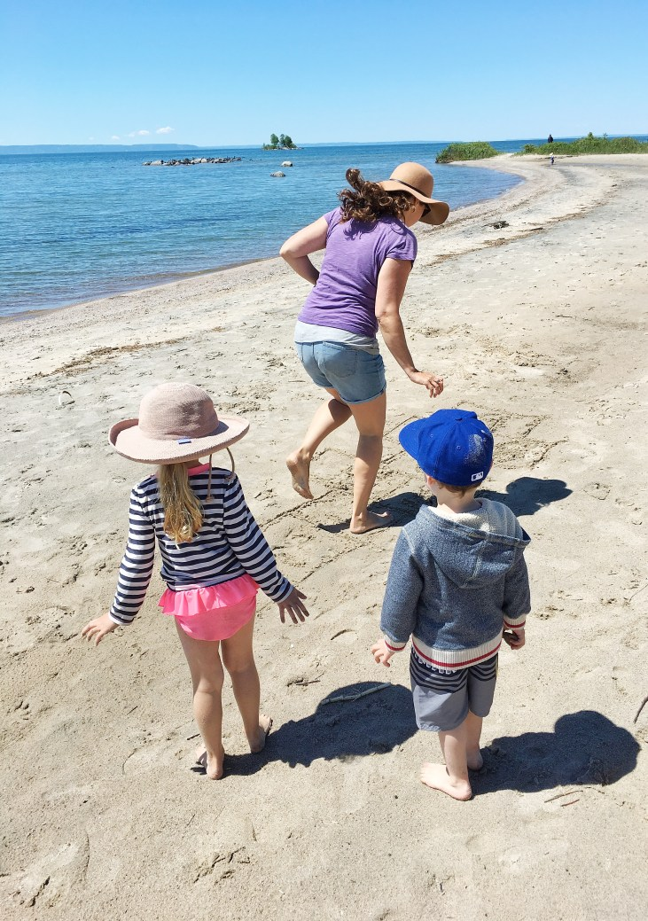 a light skinned mom playing hopscotch on the beach with a 4 year old girl and boy