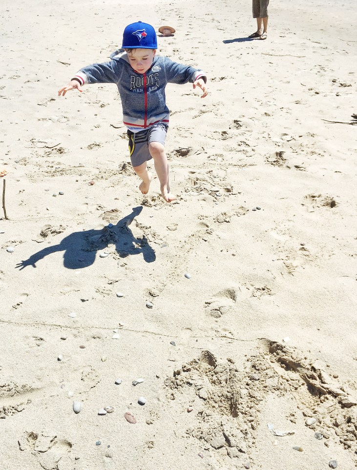 a 4 year old light skinned boy playing 'long jump' in the sand, trying to jump as far as he can from a line
