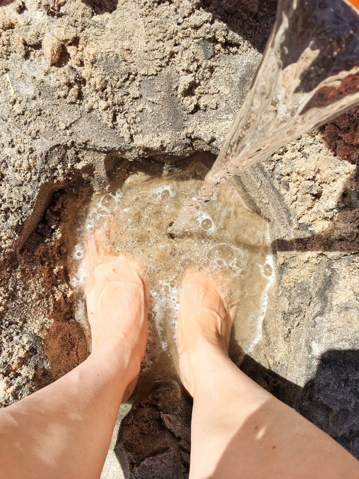 a woman's feet in a hole in the sand being filled with water