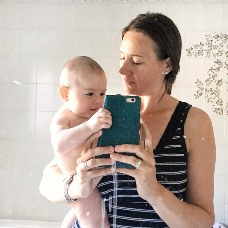 life after infertility: A browned haired, light skinned mom and a 6 month old light skinned baby girl taking a selfie in a dirty mirror