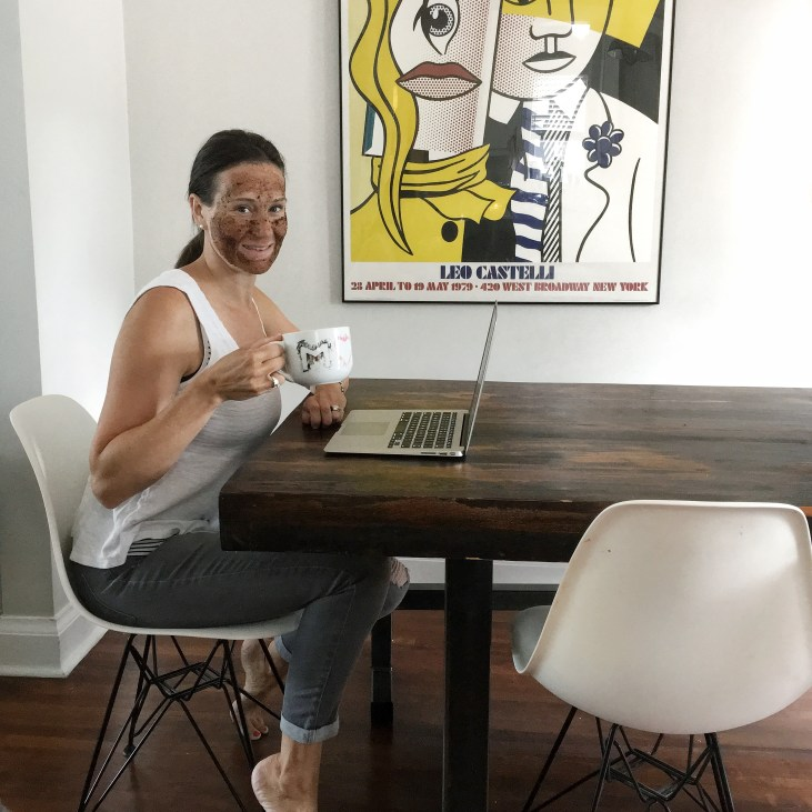 light skinned woman sitting at a dinging room table with a coffee face mask on drinking coffee and smiling