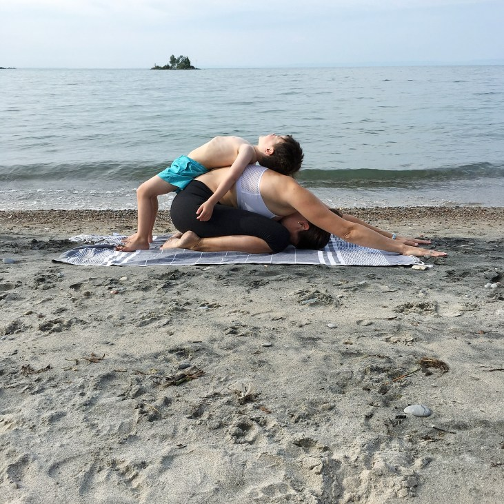 light skinned mother in childs pose with her 4 year old laying on her back, on a towel on the sand on a beach