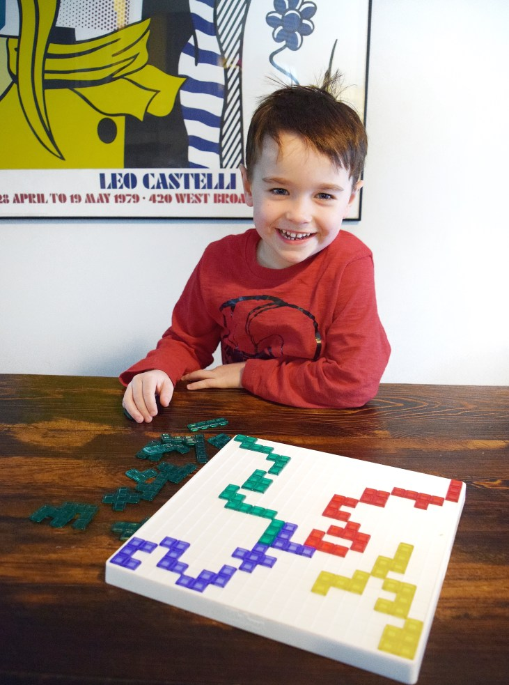 4 year old boy playing his favourite board and card game blokus