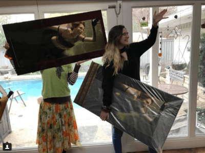 Two young, white women hold us large prints of a mermaid image.
