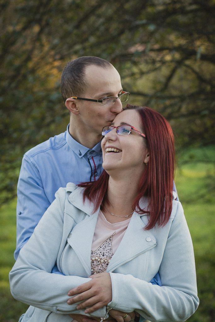 rodzice przytuleni całują się na łące
