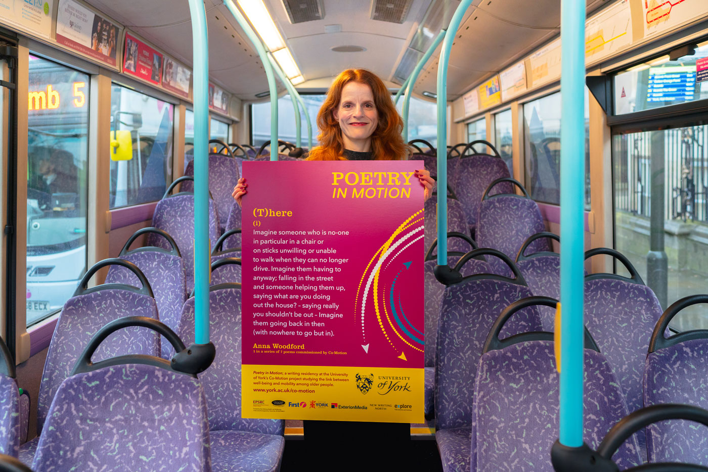 Anna Woodford stands in a First York bus aisle, holding her Poetry in Motion poster design