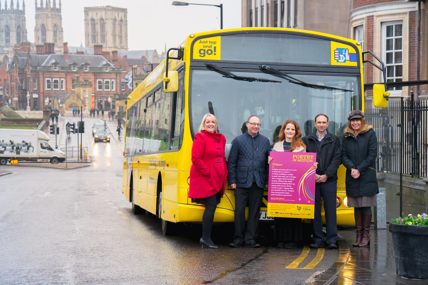Anna Woodford posing with colleagues in front of a First York bus, holding her Poetry in Motion poster design
