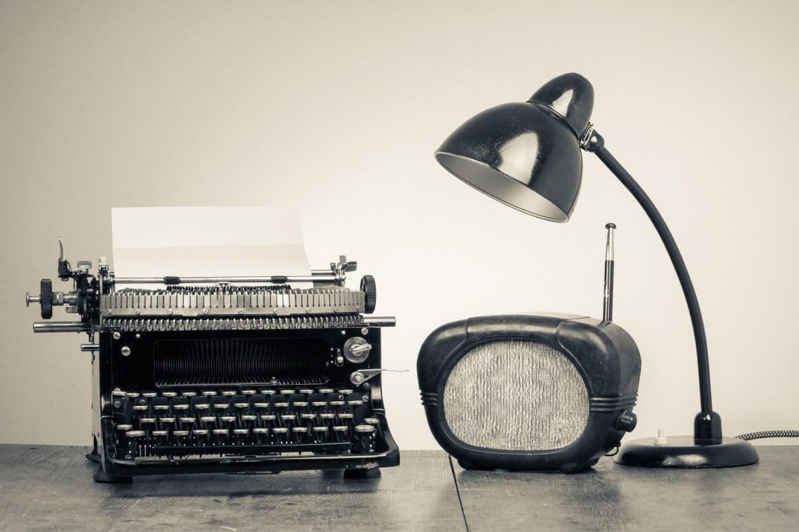 Vintage old type writer, radio and retro desk lamp on wood table