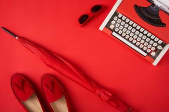 Bright red shoes, umbrella , typewriter and glasses lying on red background