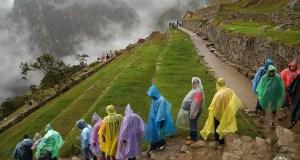 A crowd of tourists wearing rain capes in Machu Picchu