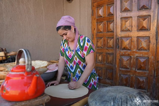 A woman wearing traditional clothes and preparing traditional uzebkistan break in Khiva