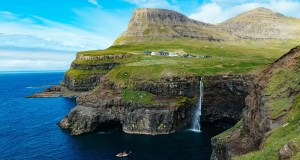 Gásadalur village with the high cliffs and the waterfall dropping into the ocean. One of the main points of interest Faroe Islands