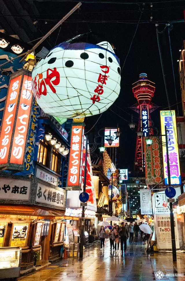 The Tsūtenkaku tower in the district of Shinsekai in Osaka seen at night, with the big blowfish lantern