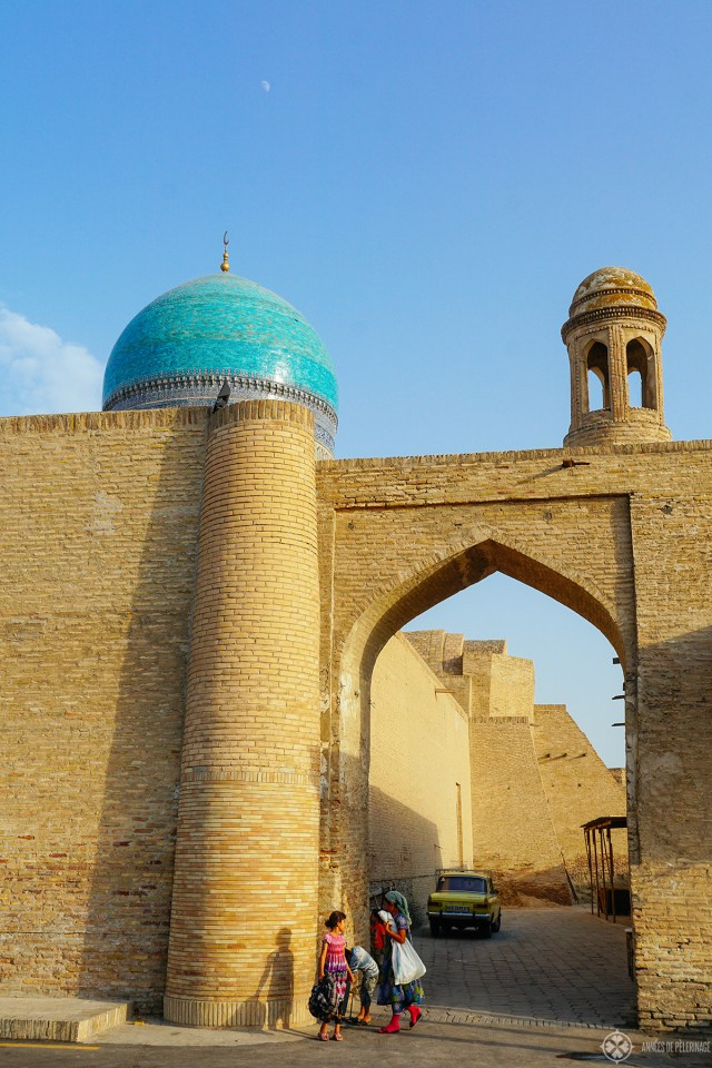 A street scene with three girls playing under an ancient arch in Bukhara Uzbekistan
