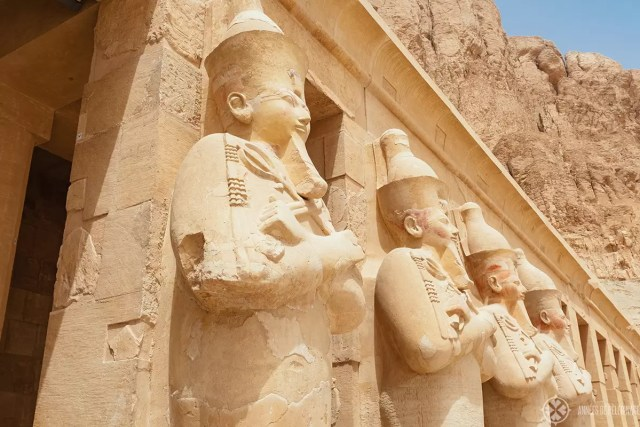 Gigantic statues of Hatshepsut standing in front of the colonades inside her temple
