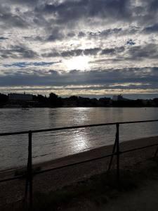Blick von Beuel über den Rhein nach Bonn bei gewitttrigem Gegenlicht und wilden Wolken