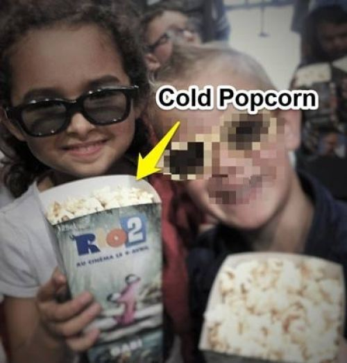 photo of my daughter holding up cold popcorn in a French movie theatre. YUCK