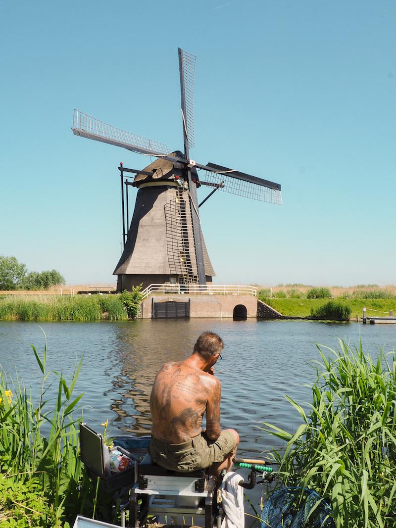 Un homme pêche devant les moulins à vent de Kinderdijk au Pays-Bas