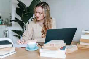 pensive businesswoman writing information in notebook near laptop and coffee