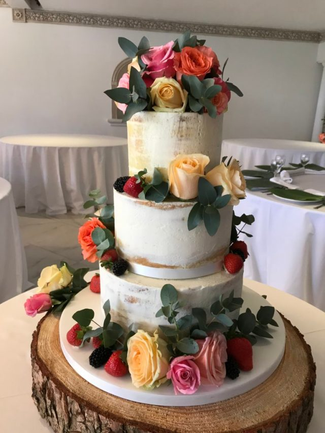 Summer Cake Trends: Semi Naked & Drip Cakes... a three tiered semi naked cake with flower arrangements