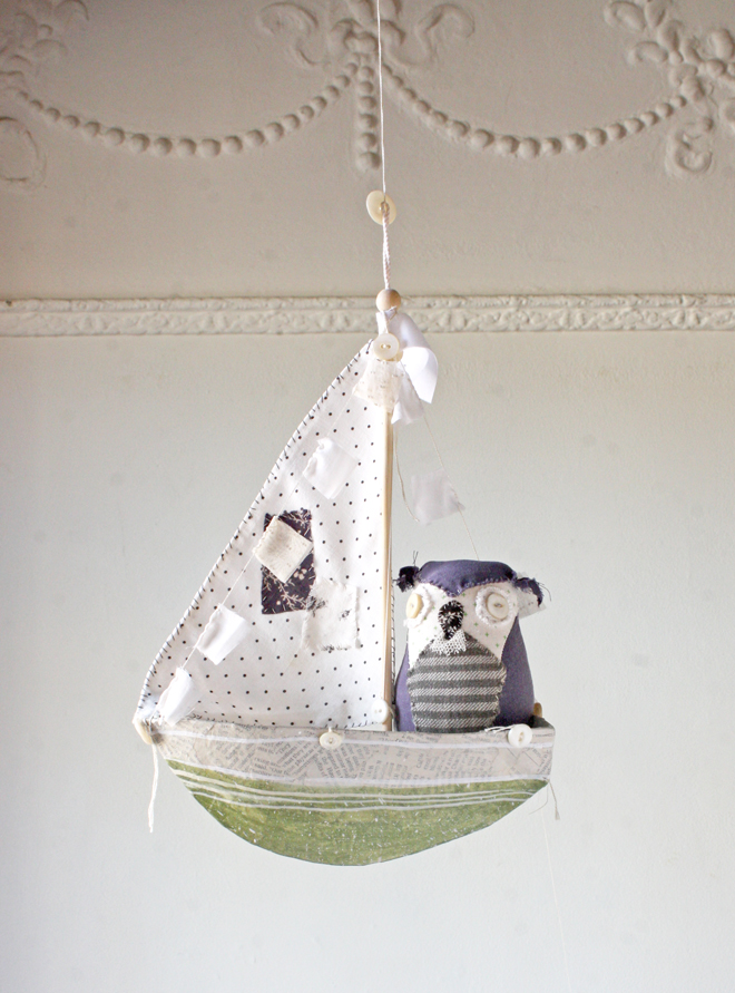 green paper mache boat with owl captain