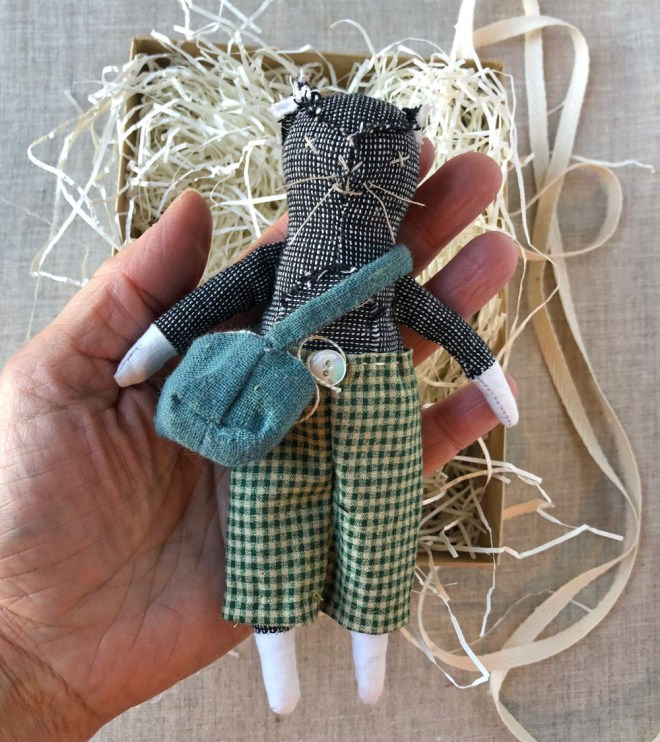 small cat rag doll with bag and pants in hand