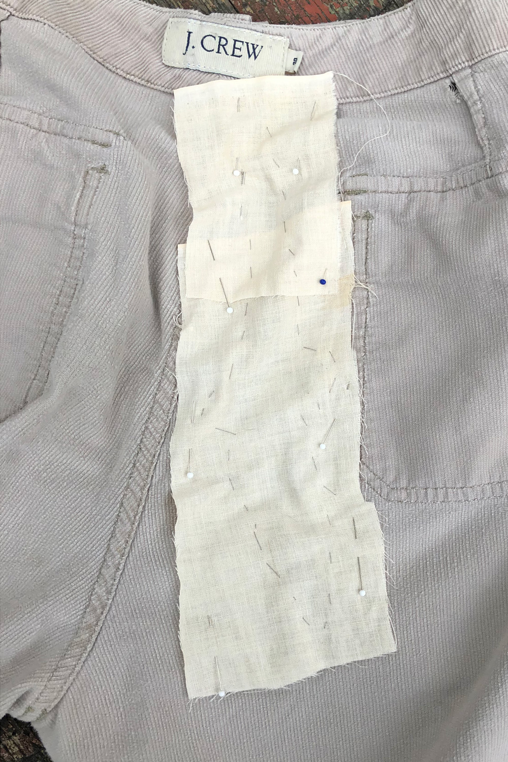fabric pinned and basted over tear in shorts - inside out