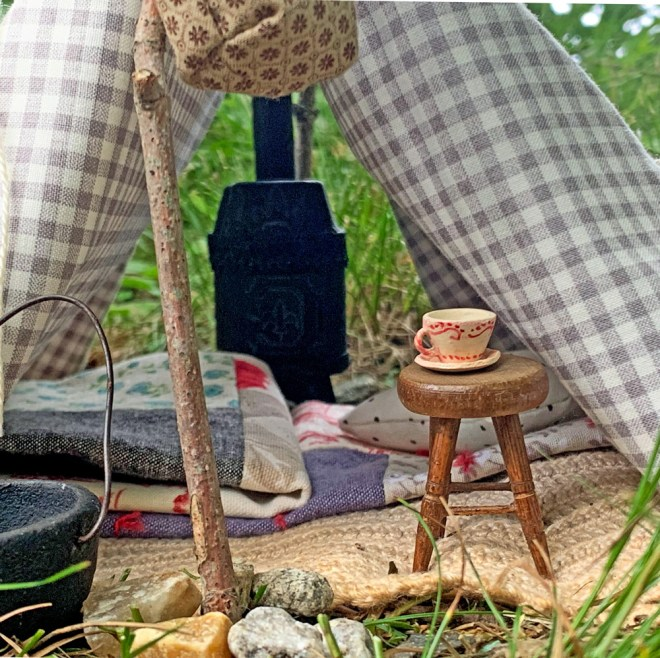 tent with ministure wood stove, teacup, stool, quilts and a pillow