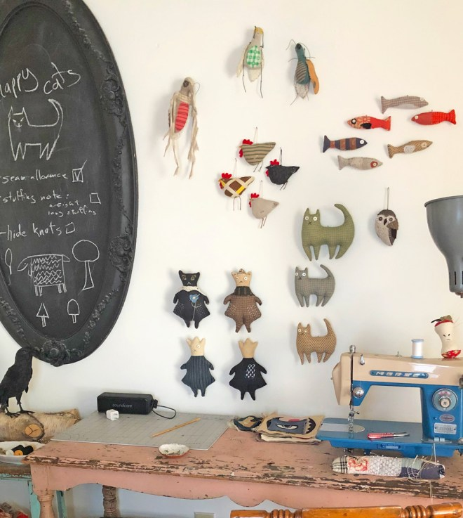 fish, cats and other small sewing prjects haung on a white wall behind a vintage sewing machine