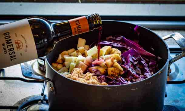 red cabbage ingredients in pot and bottle of red wine