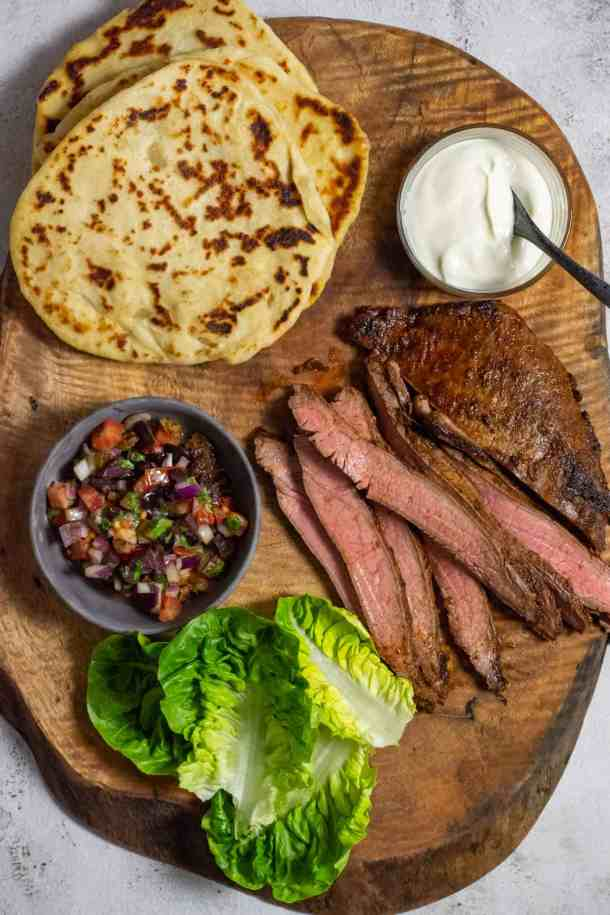 homemade pita bread, skirt steak, lettuce & salsa on wooden board