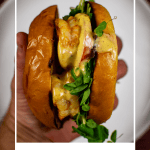 someone holding a griled prawn sandwich above a white plate