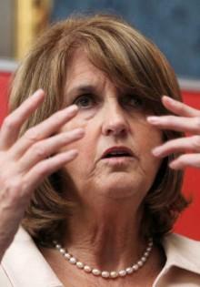 Joan Burton looking through fingers