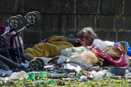 Una barbona stesa tra i rifiuti a Napoli © ANSA