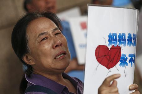 La mamma di un passeggero del volo MH370 piange e alza un cartello con la scritta: 'Mamma ti aspetta sempre! Mai abbandono la speranza' fuori dagli uffici della Malaysia Airlines oggi a Pechino © EPA