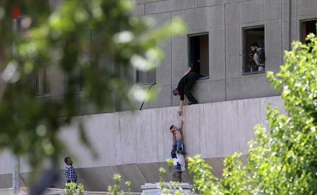 Polizia iraniana aiuta dei civili a calarsi dal Parlamento © EPA
