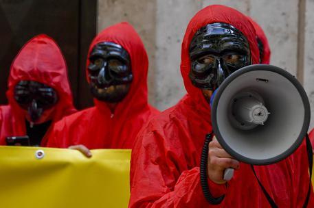 La protesta ispirata alla serie 'La casa di carta' degli attivisti del gruppo 'Massa Critica' che hanno  manifestato davanti alla sede della Banca d'Italia a Napoli, 12 maggio 2018 © ANSA