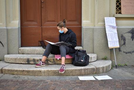 Una delle due studentesse di Torino che stanno protestando con il banco in strada contro la dad © ANSA