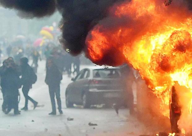 Auto in fiamme durante gli scontri a Milano © Ansa