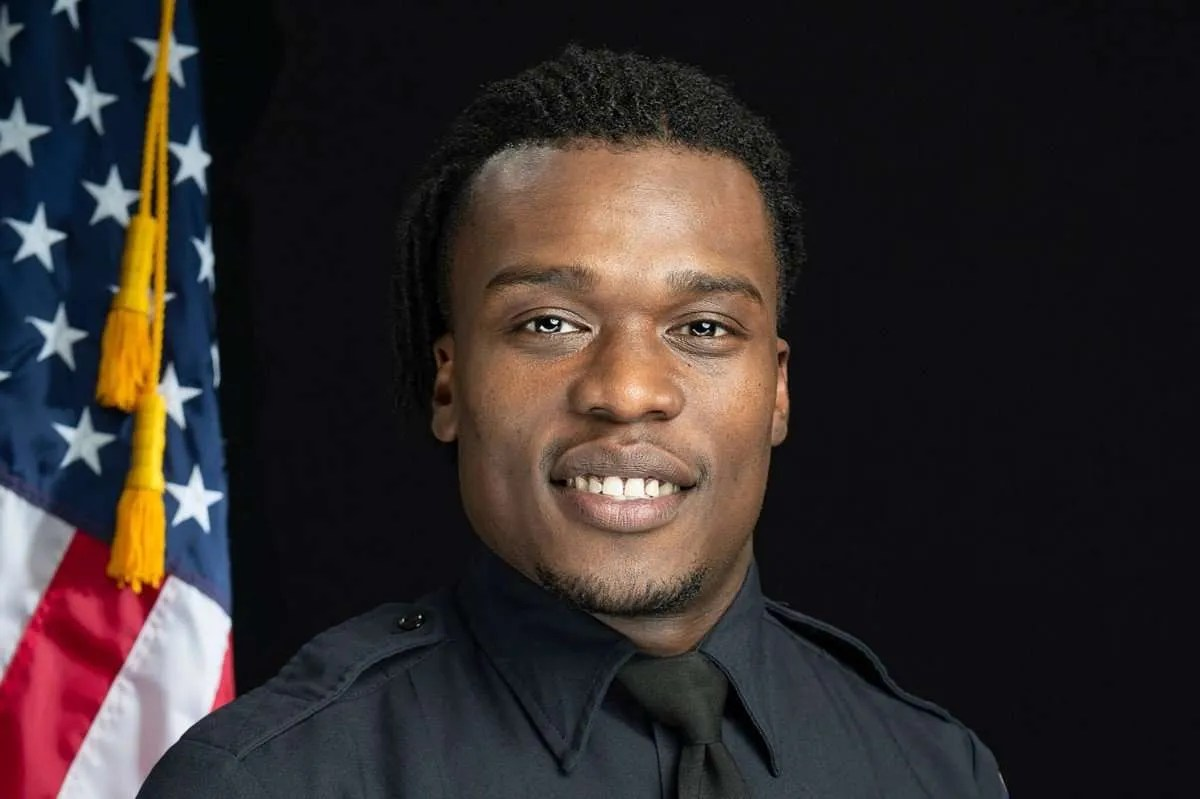 Image of Wauwatosa Police Officer Joseph Mensah in uniform with the American Flag on the left side of the background