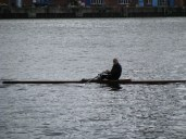A rower in Kiel getting in time between bursts of rain.
