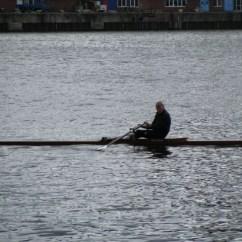 A rower in Kiel getting in time between bursts of rain.