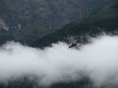 A helicopter moves building materials from Meiringen over the mountains.