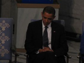 President Barack Obama listens to his introduction at the Nobel Peace Prize ceremony.