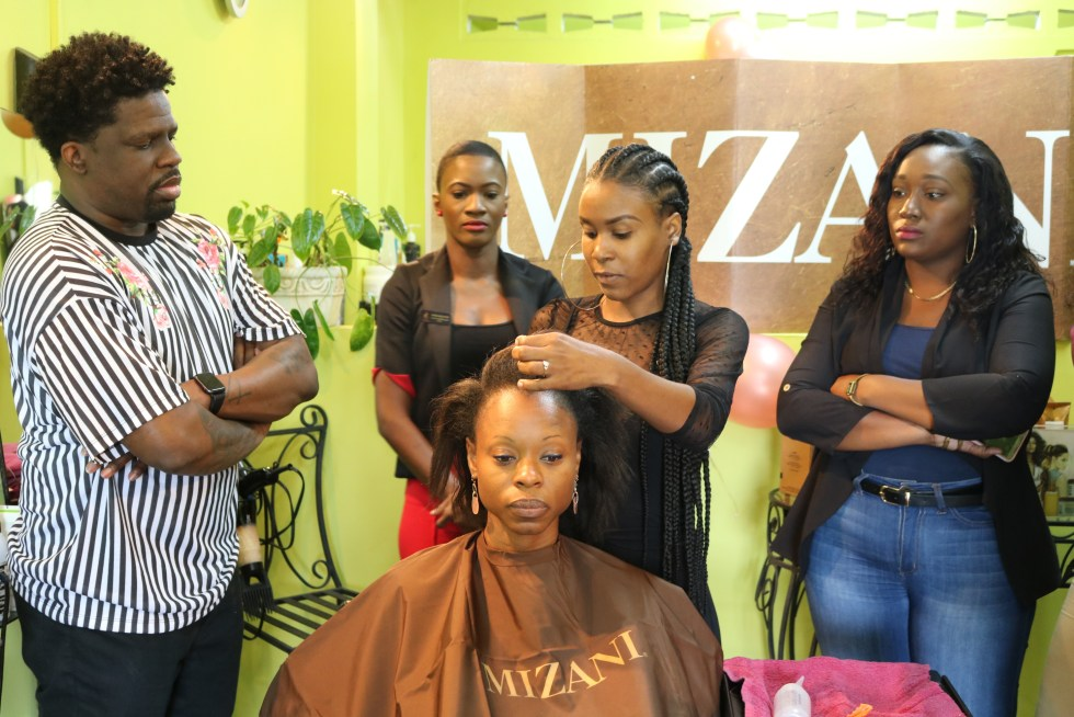 Mizani Educator Jamal Edmonds, left, looks on as stylists examine the impact of the Bond pHorce kit on a model.