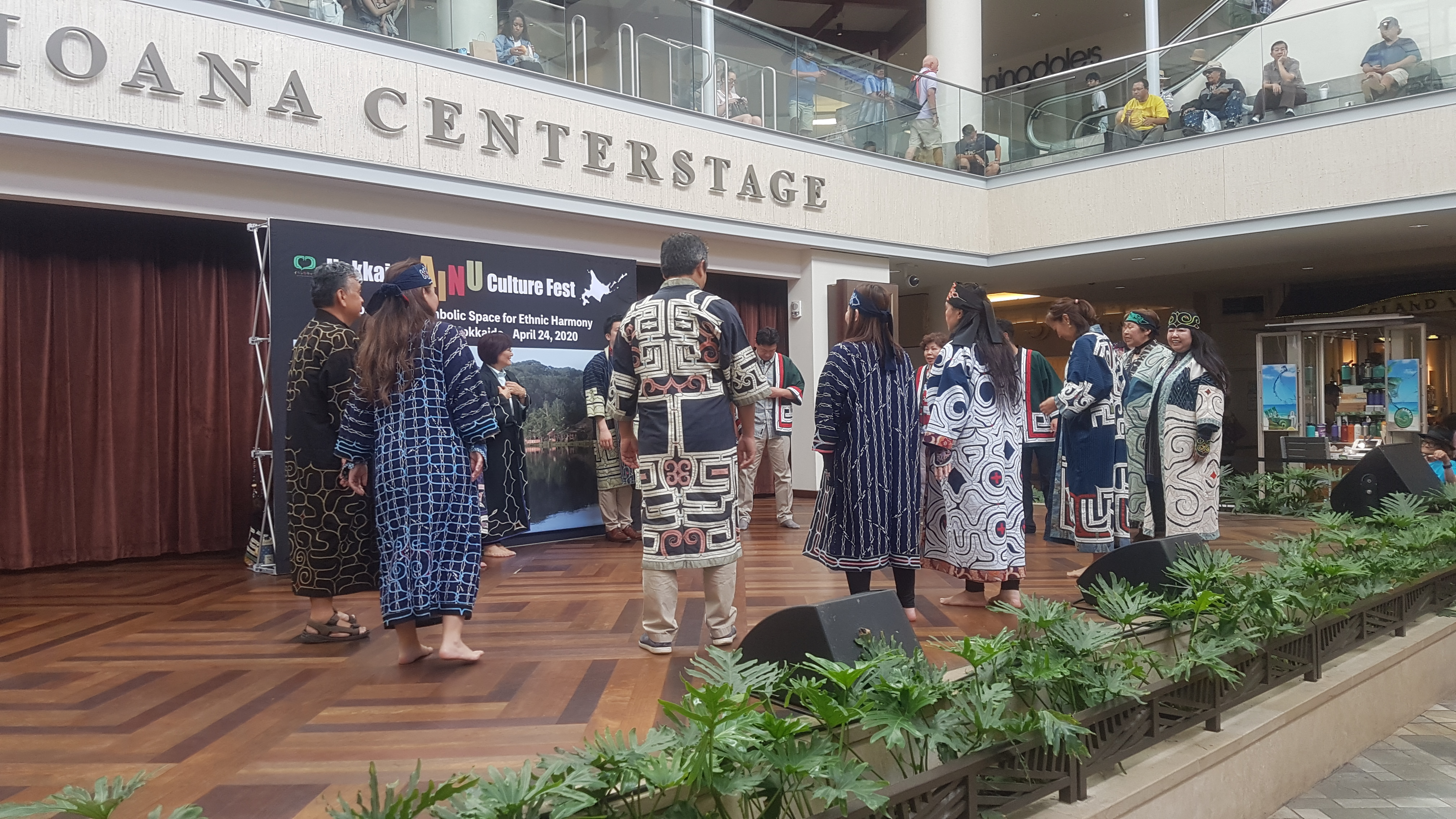 """About thirteen men and women dressed in traditional embroidered dark blue robes form a circle on a wooden stage with the words """"Ala Moana Centerstage"""" on the second floor overhang. The words are cut off and only """"centerstage"""" can be seen. Some audience members are looking at the performance from the second floor of the mall."""