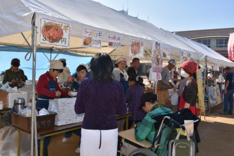 A photo of people gathering at food stands where Korean women sell Korean food at an intercultural event.