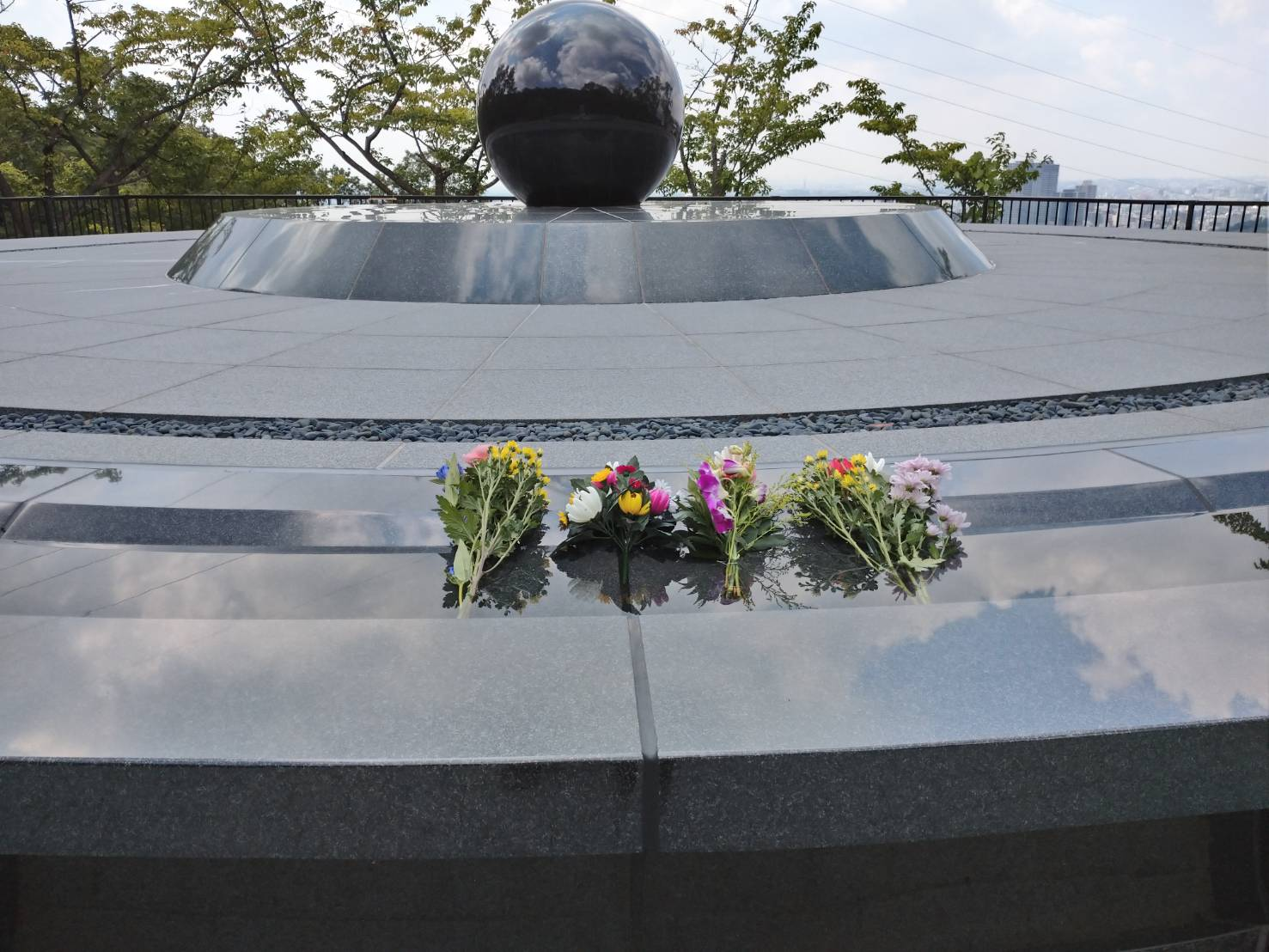 Photograph of flowers placed on a monument.
