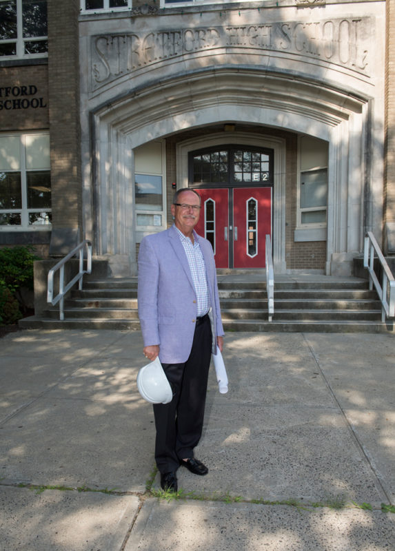 Antinozzi Associates' Geroge Perham stands before his alma mater, Stratford High School, during $125 million renovation.